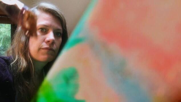 Gros plan sur le visage de Aude Ray, avec le bout de sa harpe à gauche et une toile à droite.