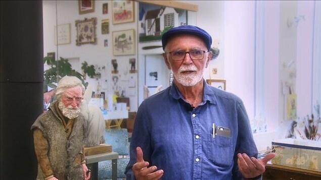 Joe Fafard avec en arrière-plan la sculpture d'un homme.