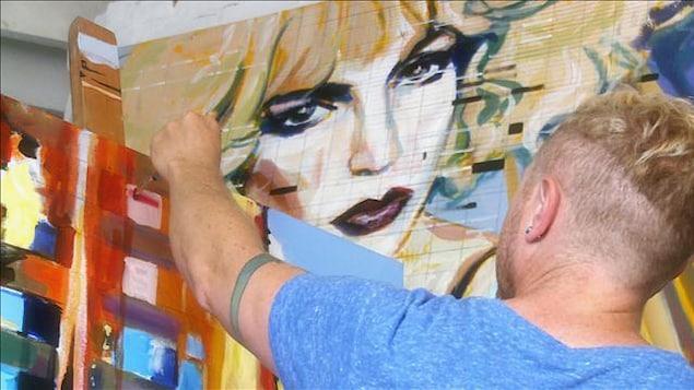 Un artiste de dos en train de peindre une toile¸¸