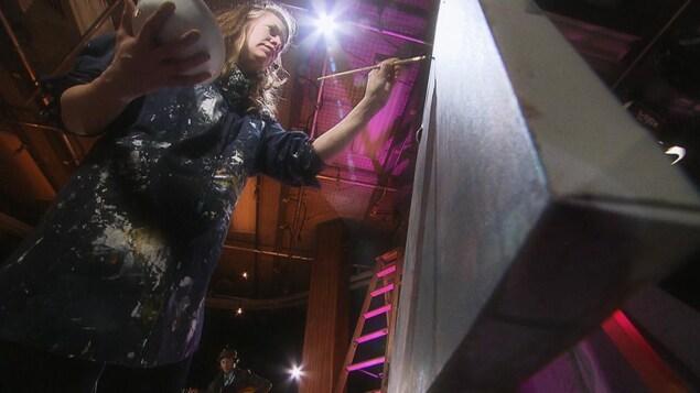 Aude Ray (de face ) en train de peindre une toile. En arrière plan, le musicien Steven Charles.