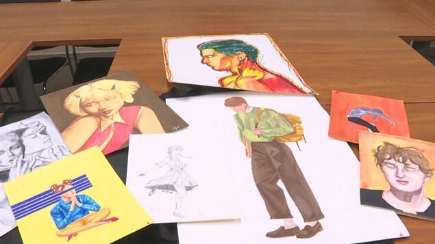 Portraits peints multicolores étalés sur une table brune.