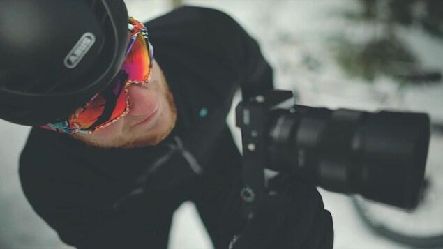Alex Cormier, en tenue de vélo, tenant une caméra