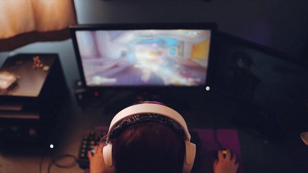 Émilie Bourloutski assise devant un ordi où on voit un jeu vidéo.