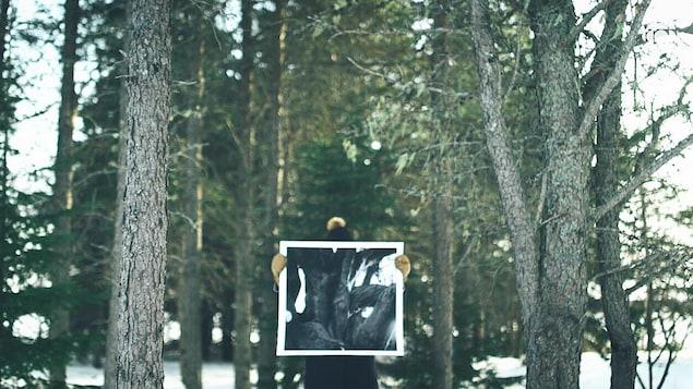 En forêt, Marika-Drolet-Ferguson cache son visage avec une de ses oeuvres où on voit un arbre.