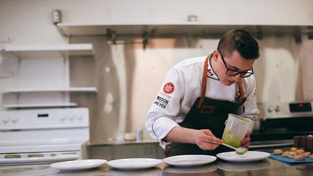 Le chef cuisinier Shane Robicheau prépare des assiettes sur un comptoir de cuisine.