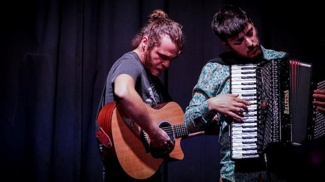 Un homme qui joue la guitare et un autre qui joue l'accordéon, sur la scène.