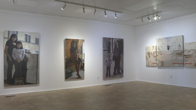 Peintures représentants des femmes et leur enfant accrochées sur un mur blanc.