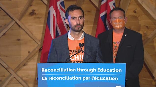 Les deux ministres en conférence de presse. Tous deux portent des chemises orange.