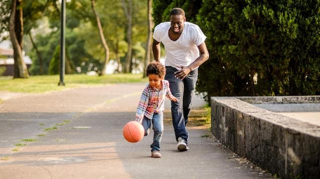 Un garçon et son père jouent au basketball.