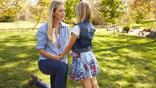 Une mère, un genou à terre, parle de très près à son enfant dans le parc.