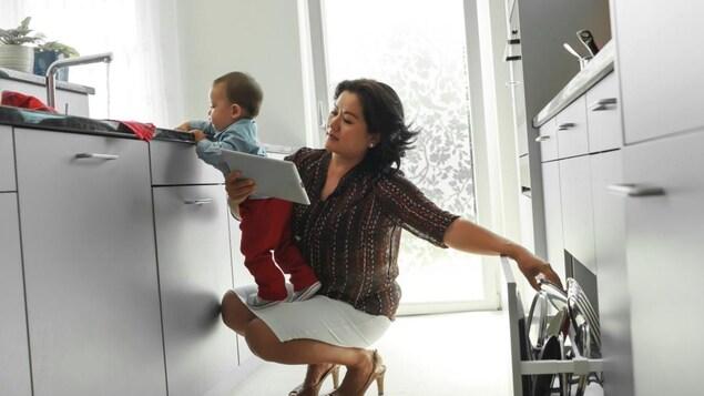 Une mère accroupie dans sa cuisine tient son enfant dans les bras, en même temps qu'elle lit sa tablette et ouvre un tiroir pour y prendre un couvercle de casserole.