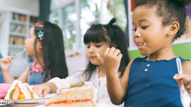 De jeunes enfants mangent un gâteau.