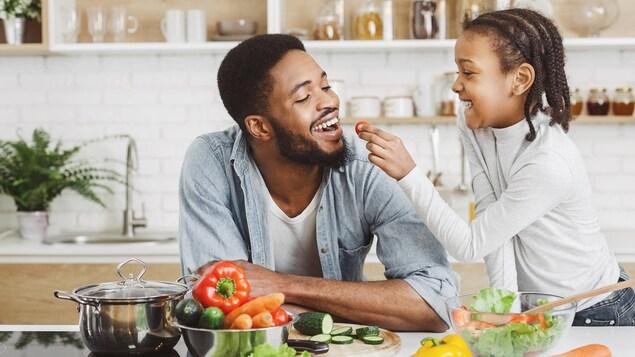 Une jeune fille offre une tomate cerise à son père.