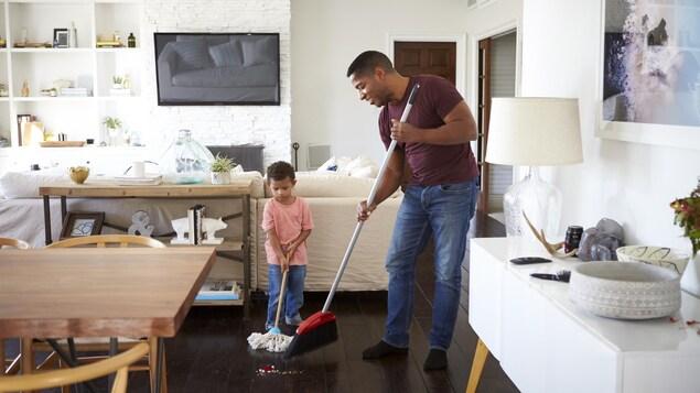 Un père et son fils passent le balai.