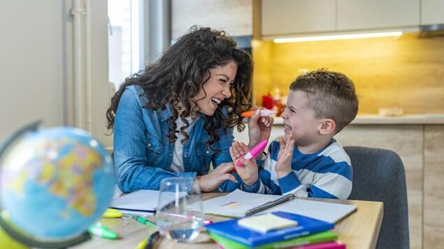 Une mère aide son fils à faire ses devoirs et leçons.