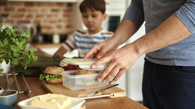 Gros plan sur un père faisant une boîte à lunch contenant un sandwich pour son fils.