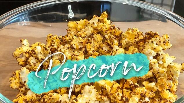 Un bol en verre rempli d'un popcorn jaune assaisonné d'une poudre foncée.