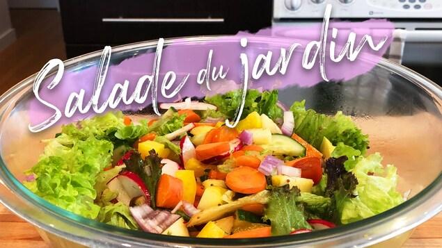 Un bol en verre rempli d'une salade de légumes frais : laitue, carottes, radis, oignons rouges, concombres, poivrons jaunes et tomates.
