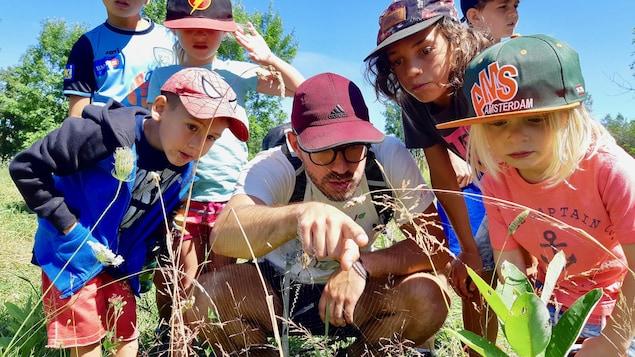 On voit 6 enfants et un animateur regarder la faune dans un parc