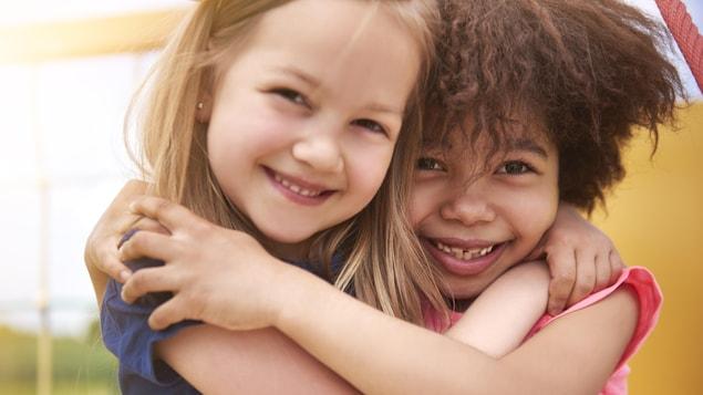 Elles ont environ 5 ans et se font un câlin. Une fillette est blanche, l'autre est noire.