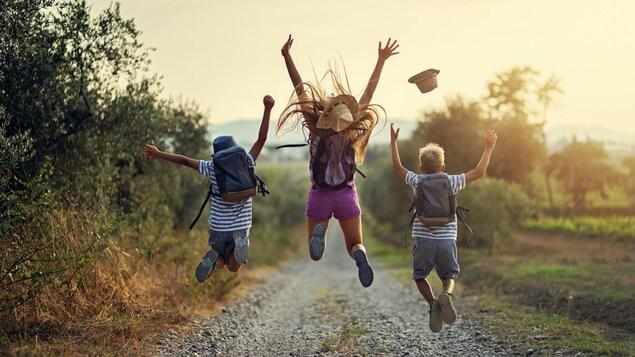 Frères et sœurs en randonnée en Toscane, Italie. Les enfants sautent de joie sur un chemin de terre.