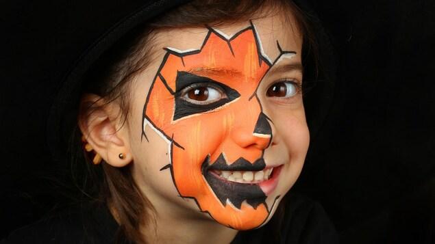 Une petite fille sourit avec le visage maquille en citrouille