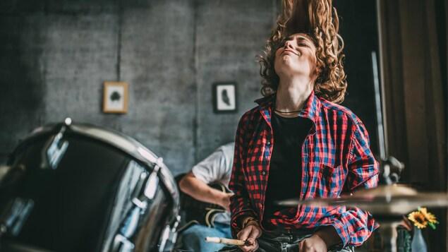 Un ado aux cheveux longs jouent de la batterie en secuant la tête