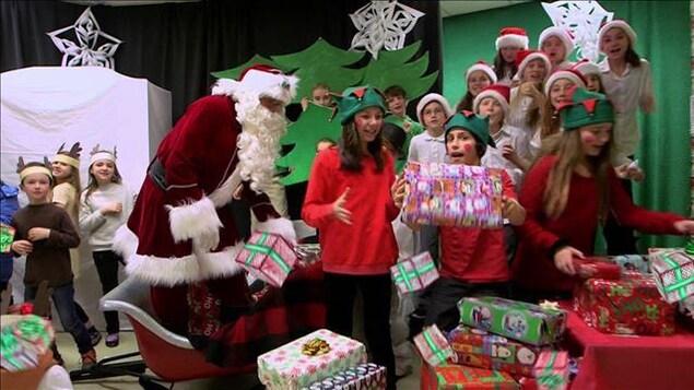 Le père Noël est dans son traîneau. Des enfants autour de lui prennent des cadeaux dans leurs mains.