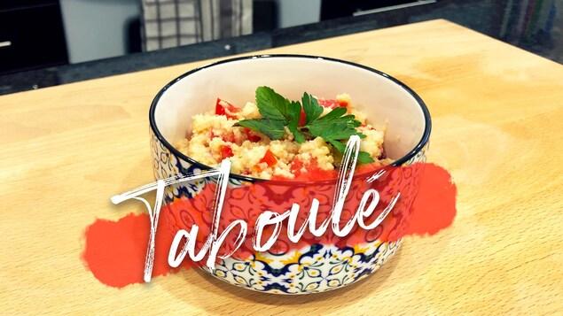 Un bol coloré rempli de couscous et de tomates en cubes garni de persil, posé sur un comptoir en bois.