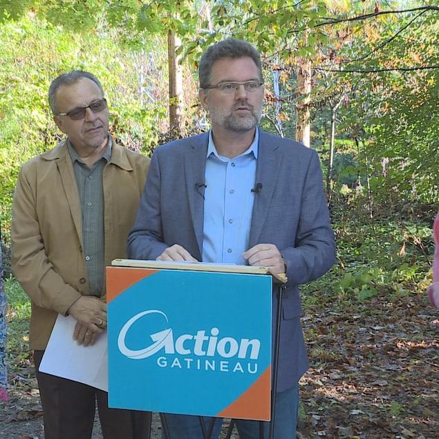 Le candidat à la mairie est derrière un lutrin du parti Action Gatineau devant une forêt. Une femme et deux hommes se tiennent à ses côtés.
