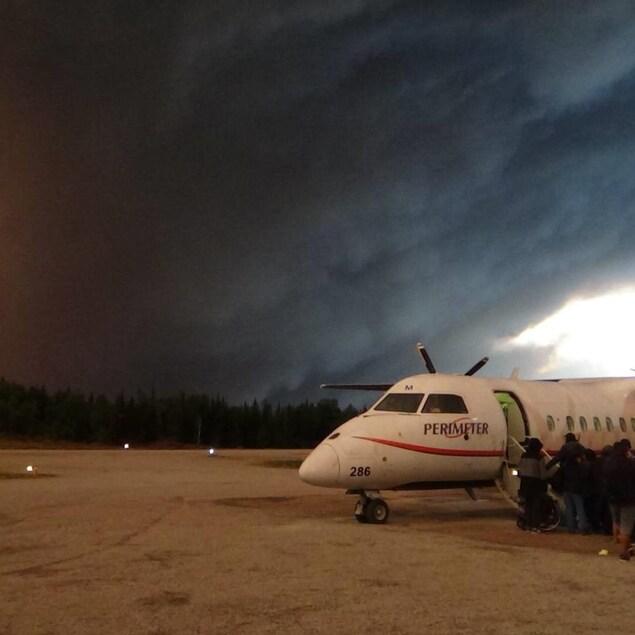 Des personnes font la file pour prendre un petit avion. Il y a une fumée épaisse.