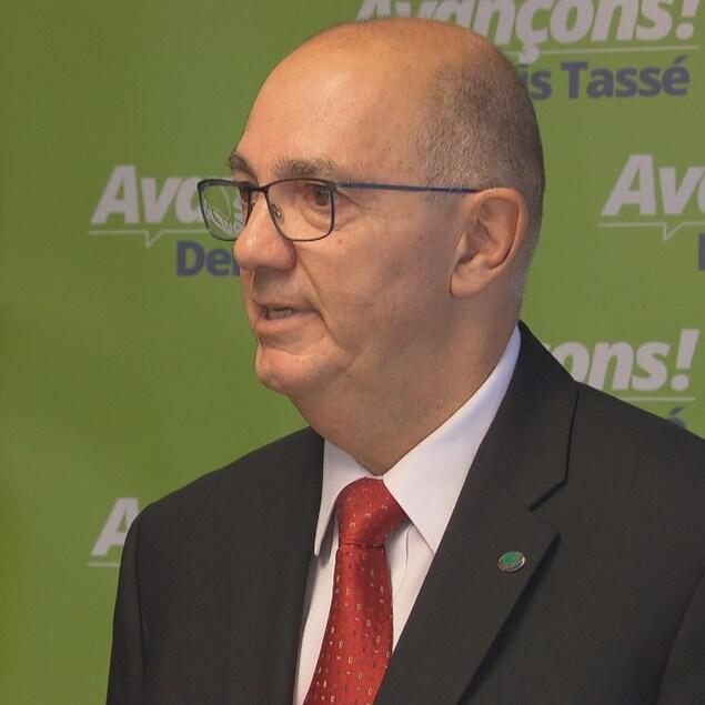 Denis Tassé en conférence de presse devant un panneau affichant son slogan « Avançons »