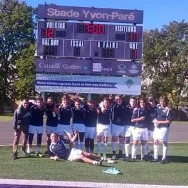 L'équipe de treize joueurs prennent la pose sur le terrain de rugby.