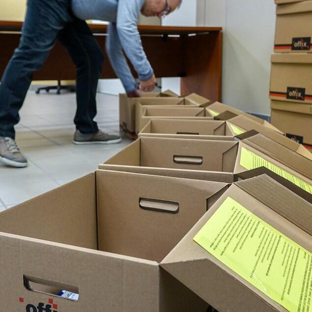 Un travailleur d'élection avec des boîtes d'équipement pour les bureaux de scrutin.