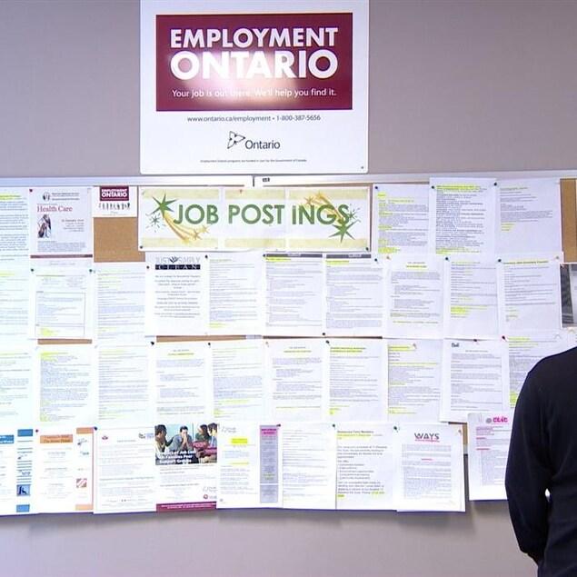 Un chômeur examine des offres d'emploi sur un babillard
