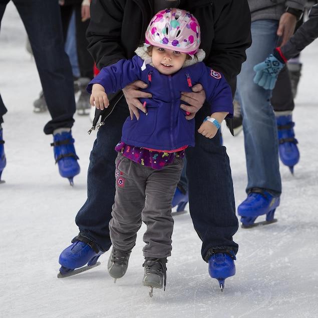 Une enfant reçoit un coup de main pour garder son équilibre en patins.