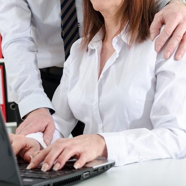 Un homme pose ses mains sur l'épaule et l'avant-bras d'une femme qui travaille à l'ordinateur.