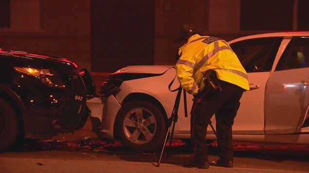 Un policier devant une voiture blanche