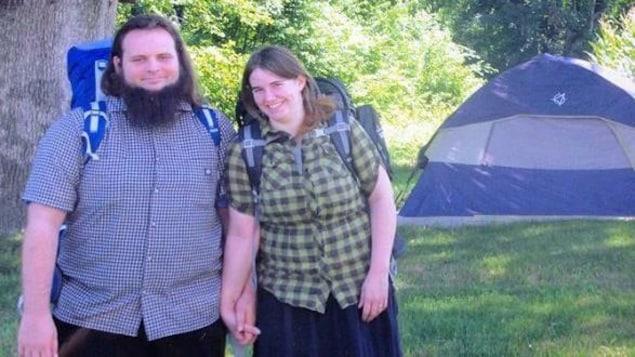 Photo de Caitlan Coleman et de Joshua Boyle qui se tiennent la main et qui portent des sacs à dos.