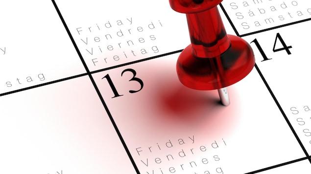 Un calendrier avec une punaise piquée dans la case du vendredi 13