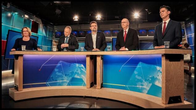 Une femme et quatre hommes devant une table, sur un plateau de télévision