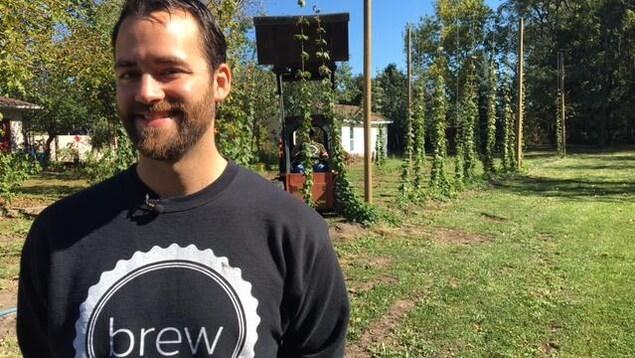 Un jeune homme barbu pose pour la caméra. Il a un grand sourire et un gilet montrant le logo de son entreprise.