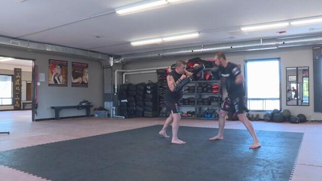 Un homme, avec des gants de boxe, frappe un autre homme qui a des gants protecteurs, pour l'entrainement.