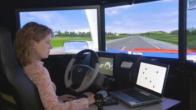 Une femme effectue une simulation de conduite dans un laboratoire de Transports Canada, à Ottawa. On peut voir un volant, un écran montrant une route virtuelle et un ordinateur.