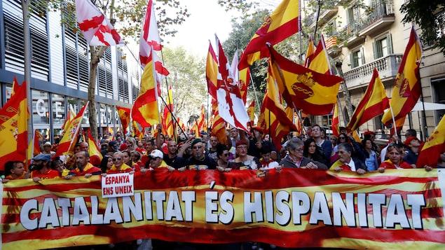Des gens marchent derrière une bannière lors d'une manifestation en faveur du maintien de l'union entre la Catalogne et l'Espagne, à Barcelone, le 8 octobre 2017.