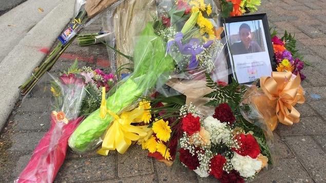 Des gerbes de fleurs déposées sur le bord de la rue en mémoire de Paulette Gagnon.