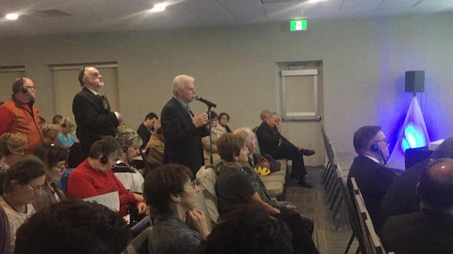 Un citoyen au micro pose une question au ministre Bourque pendant que d'autres personnes attendent en fil leur tour.