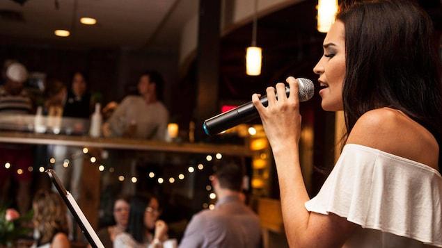 Une jeune femme vêtue de blanc chante en tenant fermement un micro.