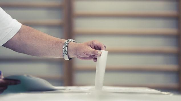 Un électeur place son bulletin de vote dans l'urne.