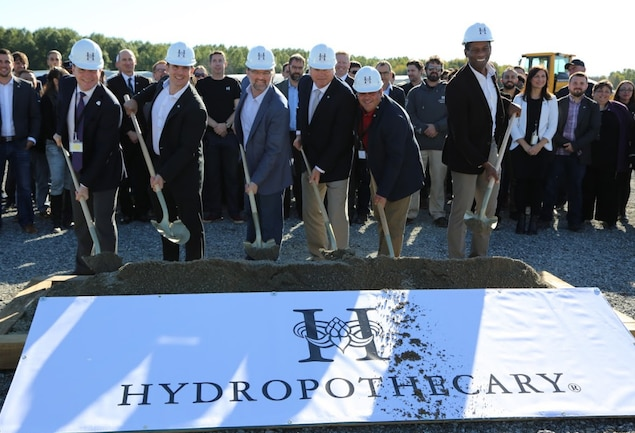 Six personnalités tiennent une pelle et lance de la terre sur une pancarte portant le nom de l'entreprise